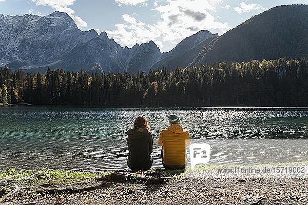Rear view of couple sitting on lakeside at Laghi di Fusine  Friuli Venezia Giulia  Italy