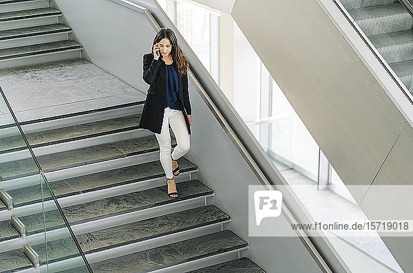 Businesswoman walking down stairs talking on the phone
