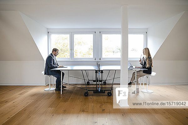 Businessman and businesswoman working at table tennis table in office