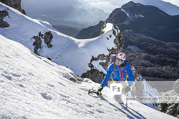 Alpinist ascending a snowy mountain  Orobie Alps  Lecco  Italy