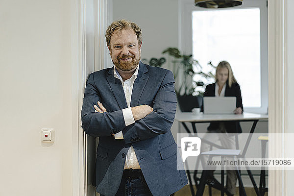 Portrait of confident businessman in office with businesswoman in background
