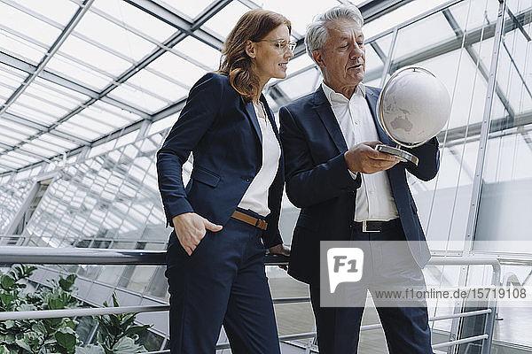 Geschäftsmann und Geschäftsfrau betrachten Globus in modernem Bürogebäude