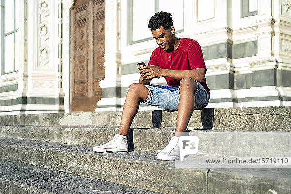 Junger Mann sitzt auf einer Außentreppe und überprüft sein Smartphone  Florenz  Italien