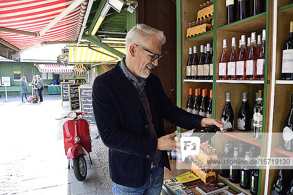 Mature man choosing bottle of wine at a wine shop