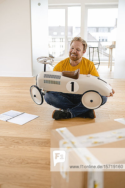 Happy man holding toy car