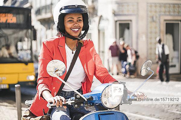 Lächelnde junge Frau fährt Motorroller in der Stadt  Lissabon  Portugal