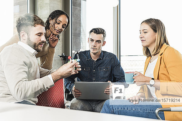 Young business people with laptop and atomic model having a meeting in office