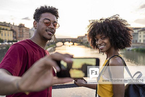 Junges Touristenpaar beim Selfie auf einer Brücke über den Arno bei Sonnenuntergang  Florenz  Italien Junges Touristenpaar beim Selfie auf einer Brücke über den Arno bei Sonnenuntergang, Florenz, Italien