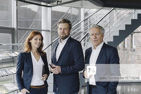 Porträt selbstbewusster Geschäftsleute in modernem Bürogebäude