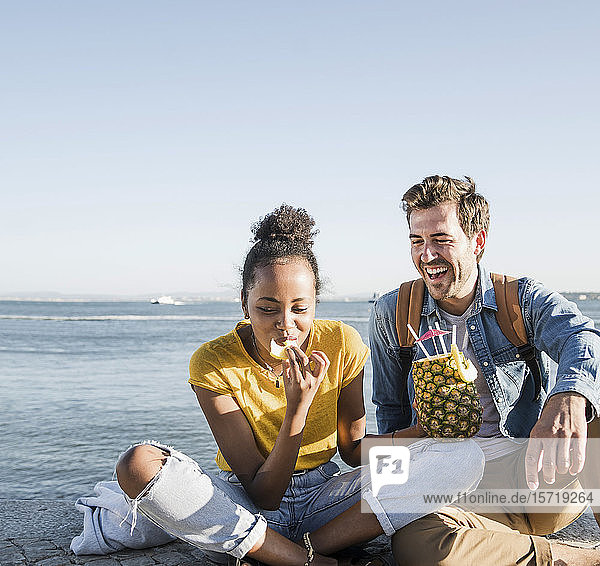 Happy young couple sitting on pier at the waterfront with a pineapple  Lisbon  Portugal