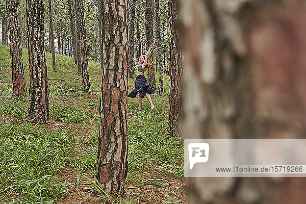 Barefoot young woman dancing in the woods