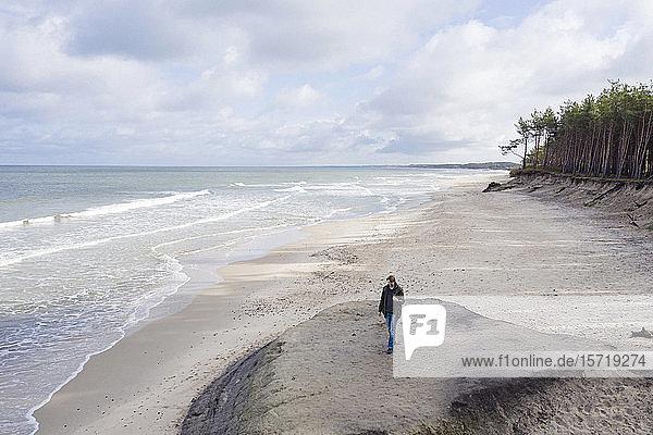 Russia  Kaliningrad Oblast  Zelenogradsk  Man walking along sandy coastal beach of Baltic Sea