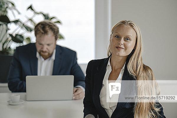 Porträt einer selbstbewussten Geschäftsfrau im Amt mit einem Geschäftsmann im Hintergrund