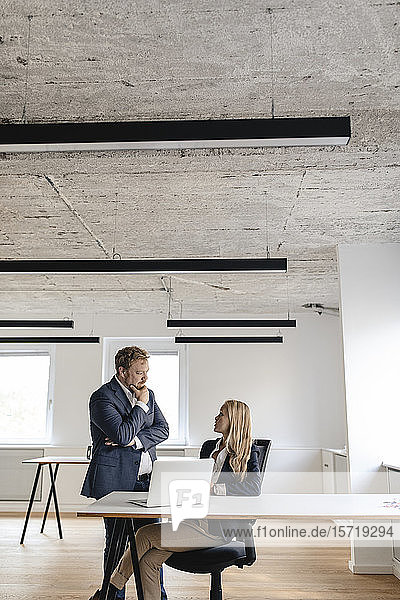 Businessman and businesswoman talking at desk in office