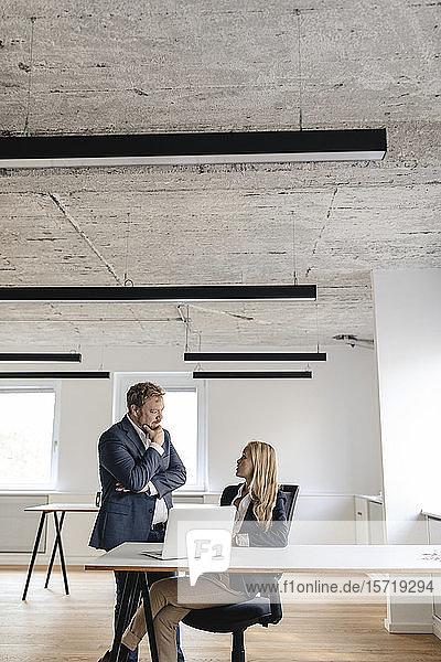 Geschäftsmann und Geschäftsfrau im Gespräch am Schreibtisch im Büro