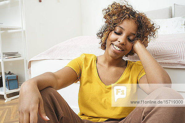 Smiling young woman listening to music with headphones at home