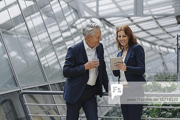 Lächelnder Geschäftsmann und Geschäftsfrau unterhalten sich in modernem Bürogebäude