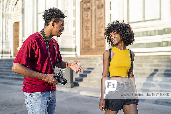 Happy young tourist couple walking and talking in the city  Florence  Italy