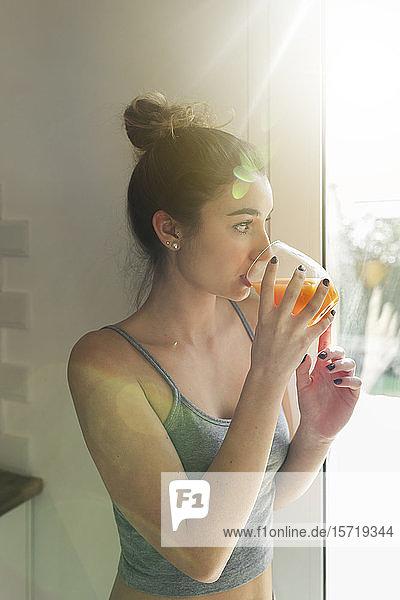Weiblicher Teenager  der Saft trinkt und aus dem Fenster schaut