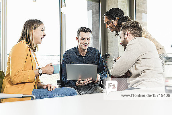 Happy young business people with laptop having a meeting in office