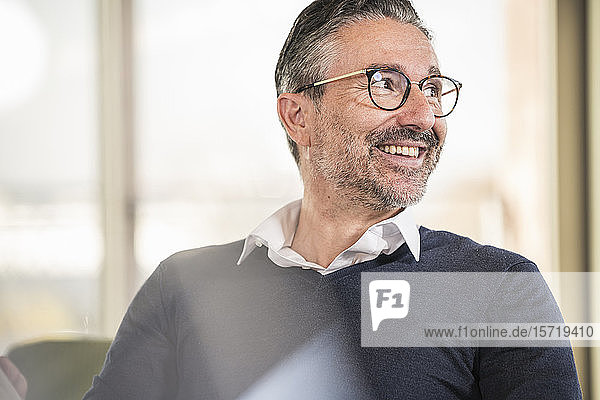 Porträt eines lächelnden reifen Geschäftsmannes im Amt  der zur Seite schaut
