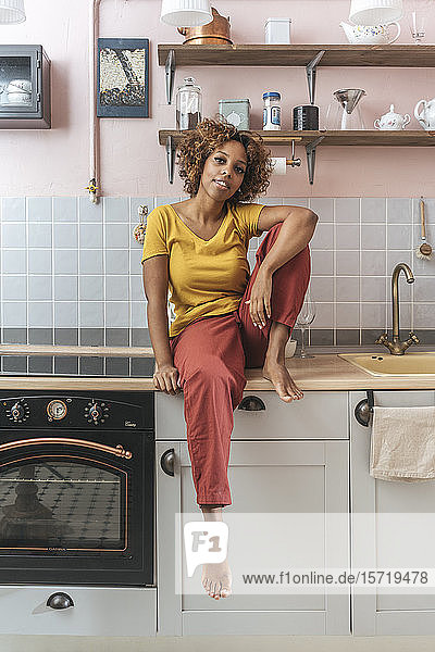 Portrait of relaxed young woman in kitchen
