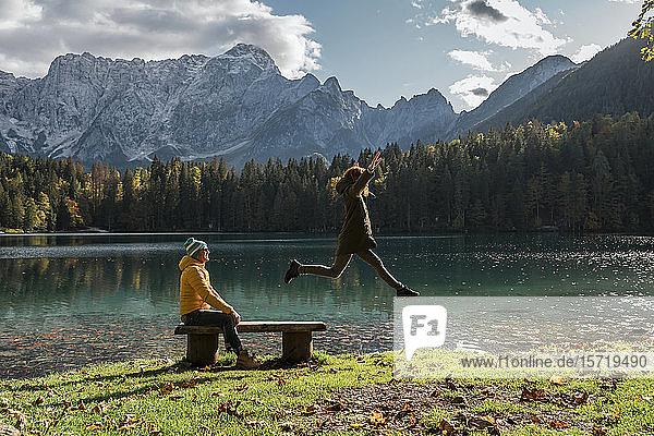 Couple at Laghi di Fusine  woman jumping from bench  Friuli Venezia Giulia  Italy