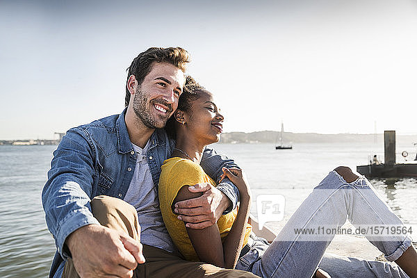 Happy young couple sitting on pier at the waterfront  Lisbon  Portugal