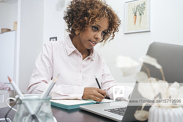 Young woman working at home taking notes and using laptop