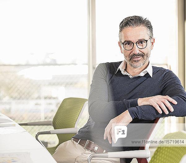 Porträt eines selbstbewussten reifen Geschäftsmannes am Schreibtisch sitzend im Büro