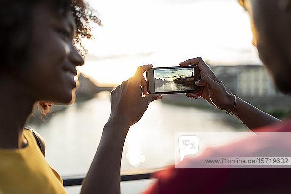 Junges Touristenpaar beim Fotografieren auf einer Brücke über dem Arno bei Sonnenuntergang  Florenz  Italien