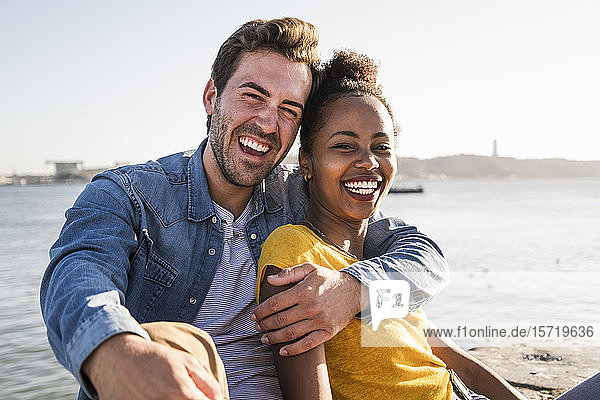 Portrait of happy young couple sitting at the waterfront  Lisbon  Portugal