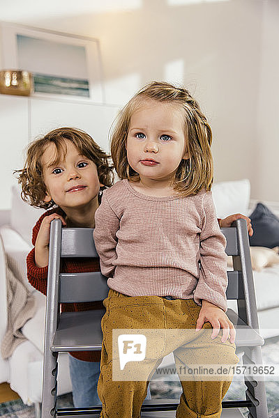 Little girl sitting on high chair at home with sister behind her
