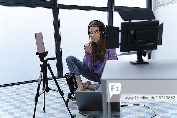 Portrait of young woman recording with laptop and smartphone in a studio