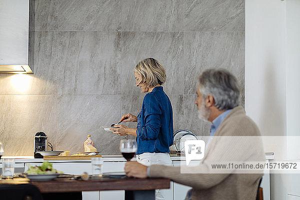 Reife Frau  die zu Hause in der Küche das Abendessen auftischt