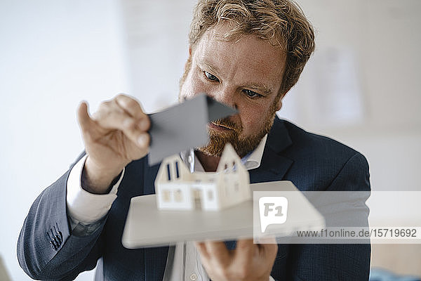 Businessman holding model house in office