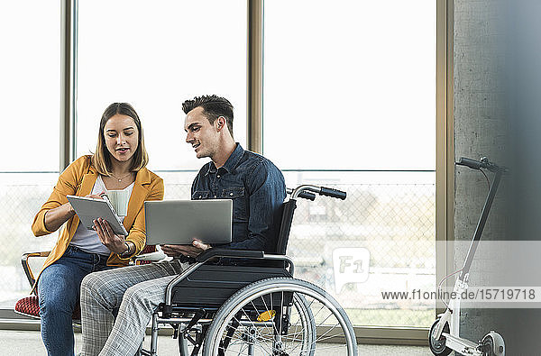 Young businessman with laptop in wheelchair and businesswoman with tablet in office