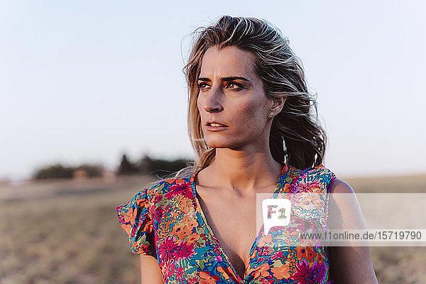 Blond woman wearing summer dress at countryside