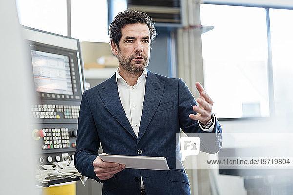 Geschäftsmann mit Tablette an einer Maschine in einer Fabrik