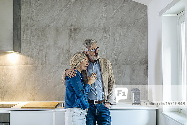 Affectionate mature couple embracing in kitchen at home