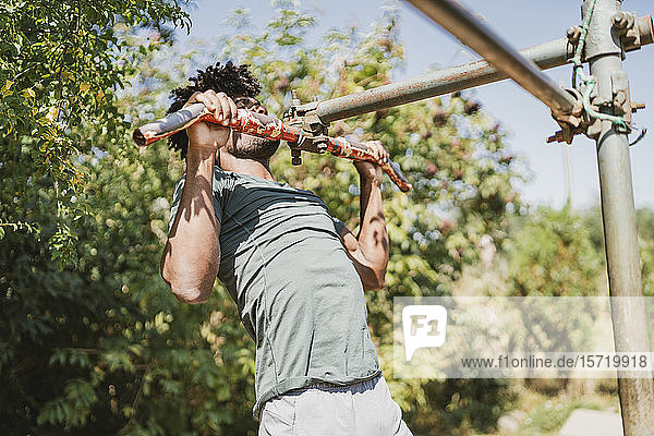 Young man during workout on a bar in a park