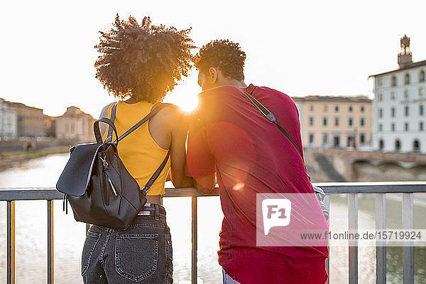 Junges Touristenpaar steht bei Sonnenuntergang auf einer Brücke über dem Arno  Florenz  Italien Junges Touristenpaar steht bei Sonnenuntergang auf einer Brücke über dem Arno, Florenz, Italien