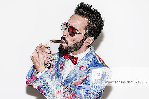 Cool and stylish man wearing a colorful suit and sunglasses lighting a cigar