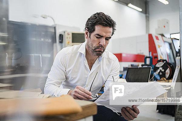 Geschäftsmann liest Zeitung in einer Fabrik
