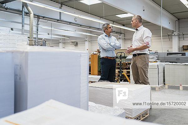 Zwei Kollegen im Gespräch in einer Fabrik