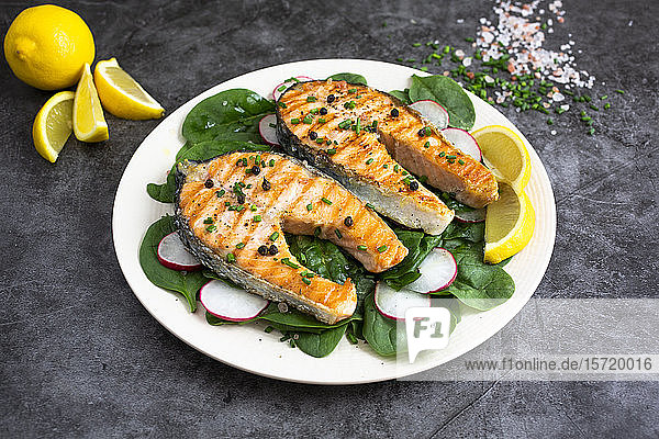 Plate of grilled salmon with lemon  radish and basil