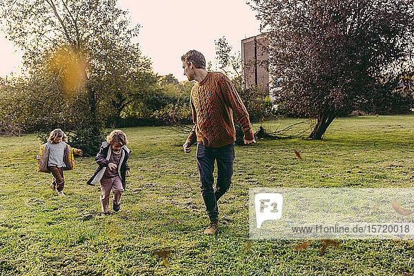 Father running with daughters on a meadow in autumn