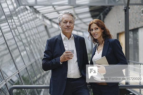 Porträt eines selbstbewussten Geschäftsmannes und einer selbstbewussten Geschäftsfrau in einem modernen Bürogebäude