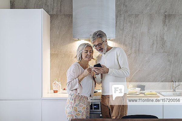 Mature couple using cell phone in kitchen at home