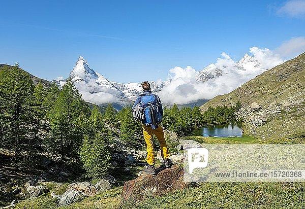 Wanderer steht auf Felsen und blickt in die Ferne  hinten Grindijsee und schneebedecktes Matterhorn  Wallis  Schweiz  Europa